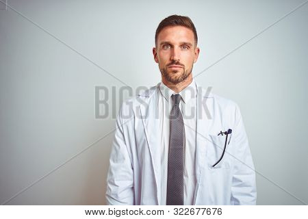Young handsome doctor man wearing white profressional coat over isolated background Relaxed with serious expression on face. Simple and natural looking at the camera.