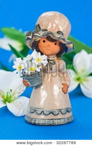 Little flower girl on blue background and white decoration flowers