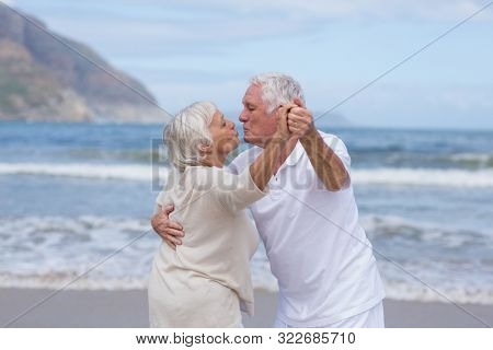 Happy senior couple having fun together at beach