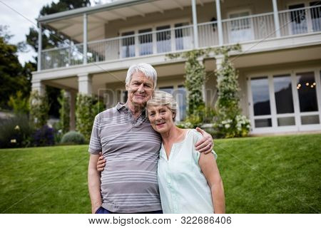Portrait of senior couple embracing each other in lawn