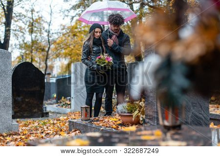 Couple mourning a deceased loved one on cemetery in fall standing between the graves