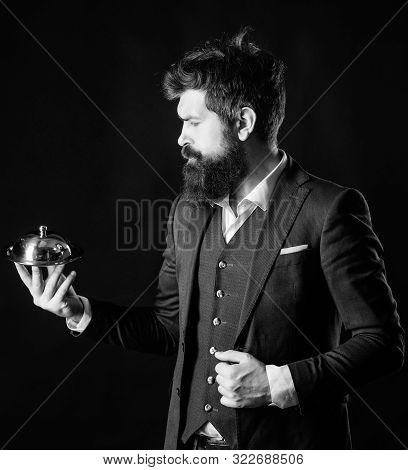 Butler concept. Servant carry metallic cloche. Man well groomed gentleman formal suit hold little cloche. Serving and presentation. Elite luxurious. Secret under cloche. Exclusive food hidden cloche poster