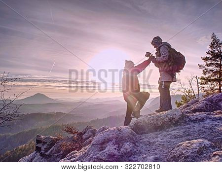 Couple Of Hikers Look Down Into Fogy Valley. Photographer Stay On Cliff And Takes Photos. Dreamy Fog