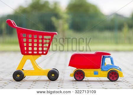Bright Plastic Colorful Toys For Children Outdoors On Sunny Summer Day. Car Truck And Shopping Pushc