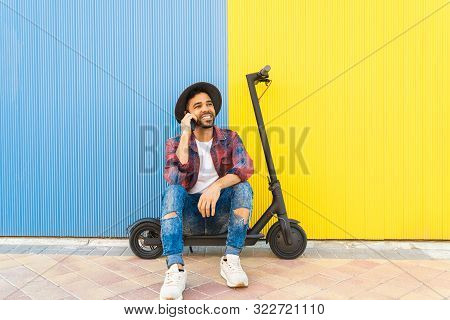 Latin Young Man Having A Phone Call While Sitting On Electric Scooter. Latin American Man Using Cell