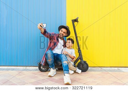 Young Father Taking A Selfie With His Son Sitting On An Electric Scooter. Divorced Father Taking Sel