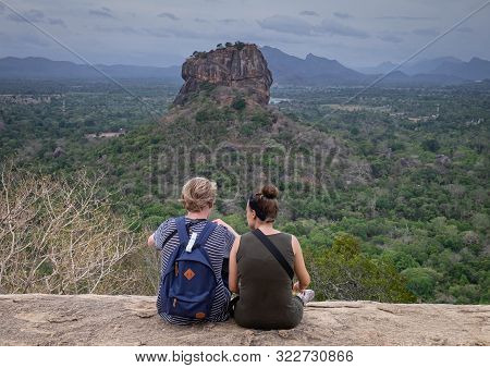 The Couple In Love On A Rock Admires The Beautiful Views At  Pidurangala Mountain.