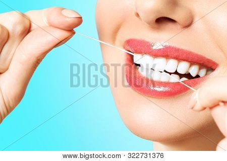 Young Beautiful Woman Is Engaged In Cleaning Teeth. Beautiful Smile Healthy White Teeth. A Girl Hold