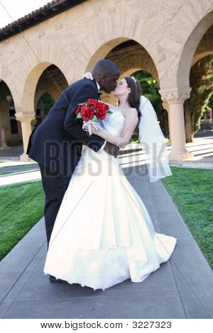 Attractive Interracial Wedding Couple Kissing
