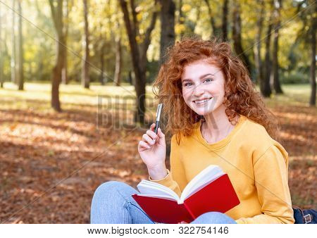 Smiling Happy Red Hair Student Girl Taking A Note Outside In Autumn Park