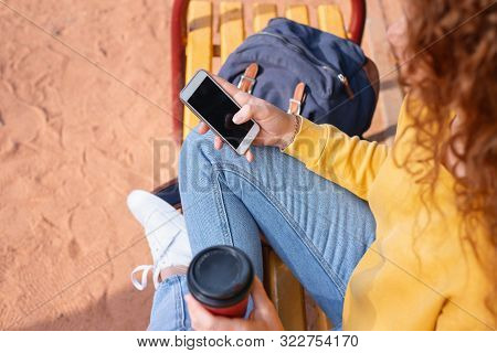 Close Up Shoot Of The Phone In Student's Girl Hand Having A Break With Coffee Outside In Autumn Park