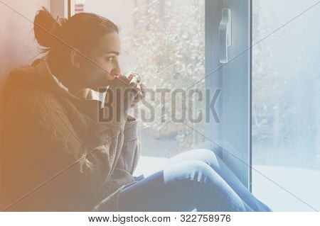 Young Brunette Woman Drinking A Cup Of Tea. Female Sitting At Home By The Window. Cold Autumn Days.