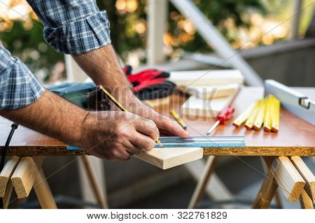 Craftsman Carpenter Adult Trace The Cut Line On A Wooden Table. Housework Do It Yourself.
