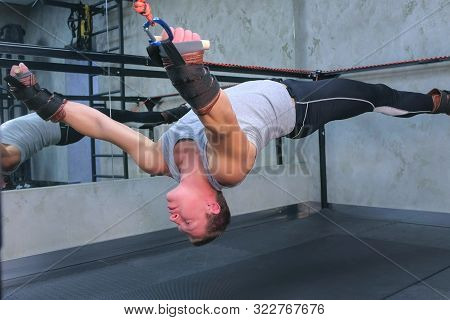 Sportsman making exercises for spine using trainer for myofascial stretching in gym raising in air. Recovery exercises rehabilitation after trauma musculoskeletal system. Professional sport equipment. poster