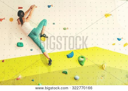 Young Athletic Woman Climbing In Boulder Gym. Back View.