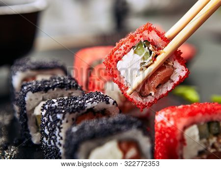 Chopsticks holding maki sushi roll with rice, cream cheese, salmon, eel, cucumber, flying fish caviar. Nori maki rolls with raw trout, red and black tobiko on natural dark stone background close up