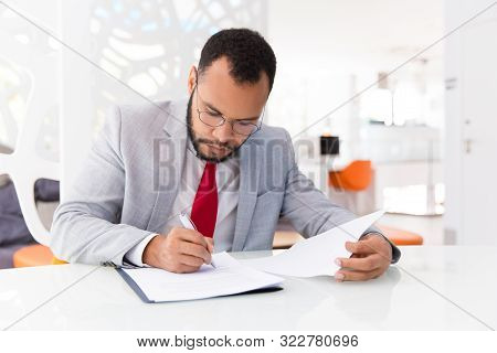 Focused Auditor Checking Document. Business Man Wearing Suit And Eyeglasses, Signing Contract. Docum