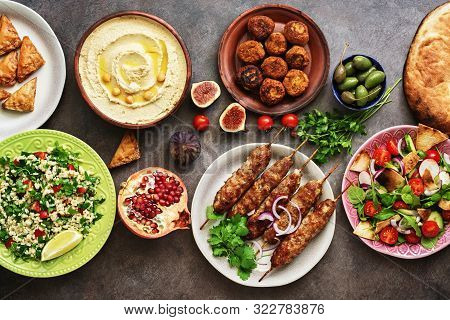 Arabic And Middle Eastern Dinner Table. Hummus, Tabbouleh Salad, Fattoush Salad, Pita, Meat Kebab, F