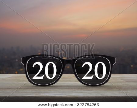 2020 White Text With Black Eye Glasses On Wooden Table Over Blur Of Cityscape On Warm Light Sundown,