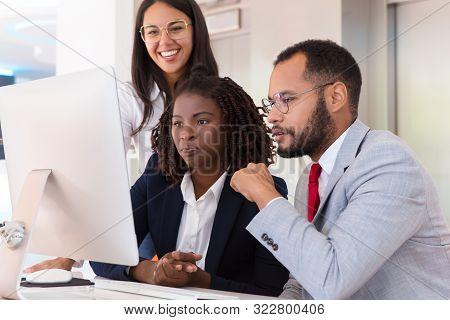 Excited Diverse Business Team Watching Video On Desktop. Business Man And Women Sitting At Table, Us