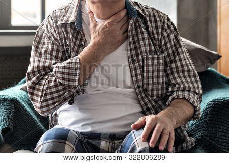 Senior Man With Throat Pain Sitting On Sofa.