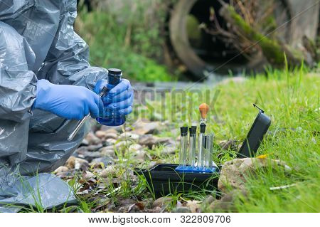 A Worker In A Protective Suit Takes Samples Of Water And Soil For Contamination