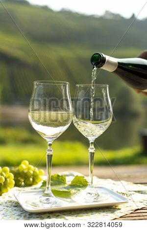 Waiter Pouring  German Quality White Wine Riesling, Produced In Mosel Wine Regio From White Grapes G
