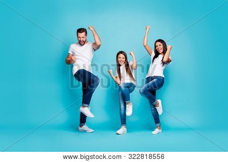 Full body photo of daddy mommy and small lady raising fists air rejoicing wear casual outfit isolated blue background poster