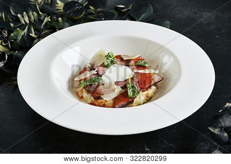 Exquisite Serving White Restaurant Plate of Risotto with Pecorino Cheese and Warm Roast Beef. Beautiful Delicacy Italian Veal Paella on Dark Stone and Leaves Background