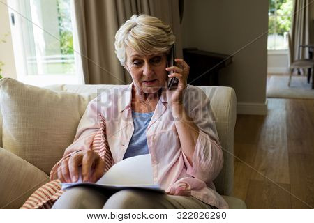 Senior woman talking on mobile phone while checking a document in living room at home