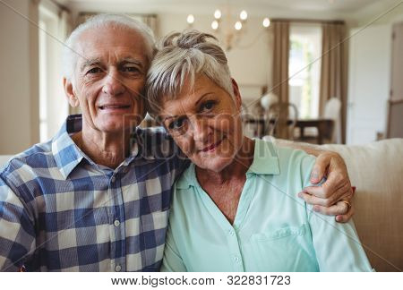 Portrait of senior couple relaxing on sofa in living room at home