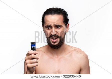 Unsure Bearded Man With Mustache Looks At The Electric Shaver Standning Bare Isolated Over White Bac