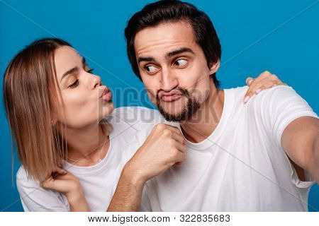 Happy Couple Of A Young Blond Woman And Brunet Bearded Man With Mustaches In White T-shirts And Blue