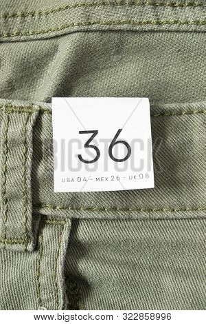 36 size clothes label on khaki green denim background poster