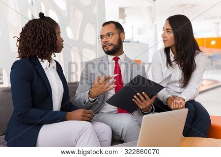 Legal Expert Explaining Document Details To Colleagues. Business Man And Women Sitting On Office Cou