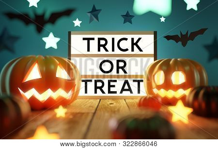 Halloween Table Decorations With Glowing Pumpkin Lanterns And A Lightbox With Trick Or Treat Message