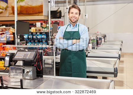 Smiling cashier or salesman in green apron at the supermarket cashier