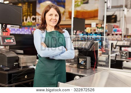 Smiling cashier in the supermarket stands with folded arms at the cash register