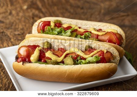 Two Classic Hotdogs In Buns On A Plate