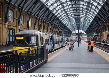 LONDON,UK -AUGUST 16,2019 : Passengers and trains at the platform at King's Cross station in London