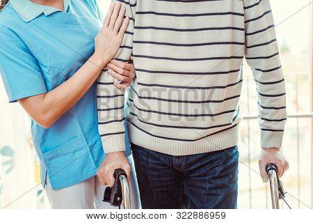Smiling nurse helping senior man with walking frame in the nursing home
