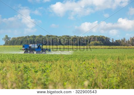 Large agricultural sprayer spraying a larger field or potatoes in rural Prince Edward Island, Canada.