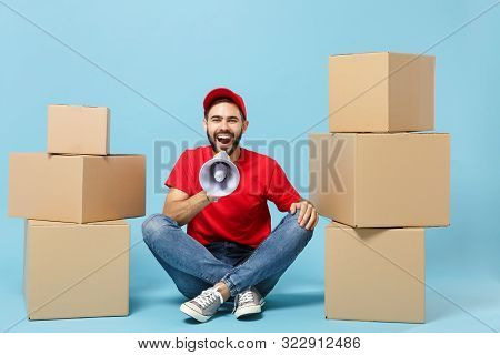 Delivery Man In Red Uniform Isolated On Blue Background, Studio Portrait. Male Employee In Cap T-shi