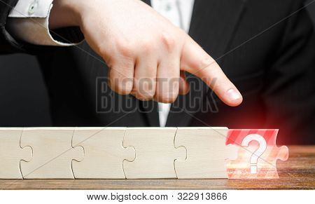 Businessman Finger Points To The Absence Of A Component In The Puzzle Chain. Missing Or Missing Comp