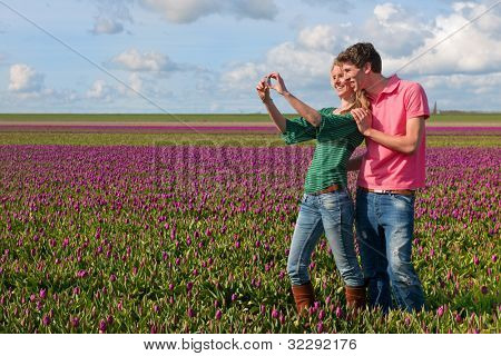Couple Dutch tourists are taking pictures in the flower fields
