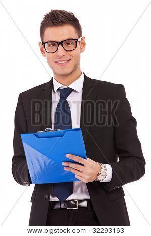 Junge lächelnd Geschäftsmann, die Brille ist in Zwischenablage schreiben.
