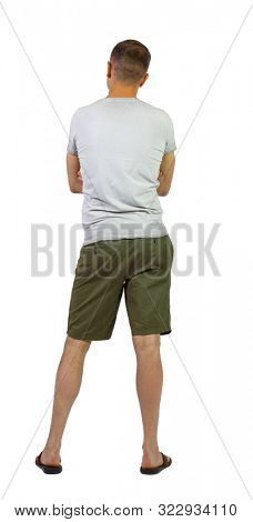 Back view of young manin shorts looking. Rear view people collection. backside view of person. Isolated over white background. The guy in the shorts thoughtfully crossed his arms over his chest.