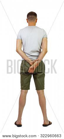Back view of young manin shorts looking. Rear view people collection. backside view of person. Isolated over white. A guy in shorts and slippers stands with his hands clasped behind his back.