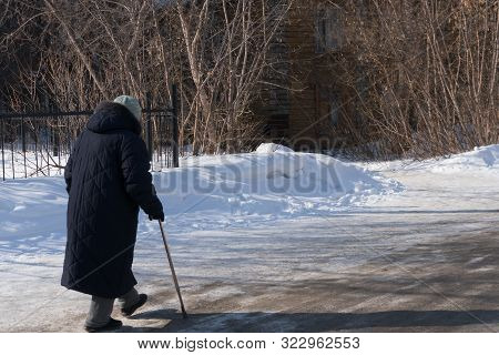 Back View Of Elderly Women Walking Along A Slippery Winter Road With A Cane. Concept Elder Day, Take