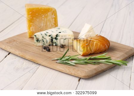 Cheese Of Different Varieties On A Wooden Board, White Wooden Table. Assorted Cheeses On Wooden Cutt